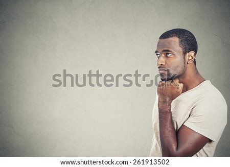 Portrait sad, depressed, worried young man looking up isolated on grey wall background. Human face expressions, emotion, feelings, reaction, life perception, mistakes - stock photo