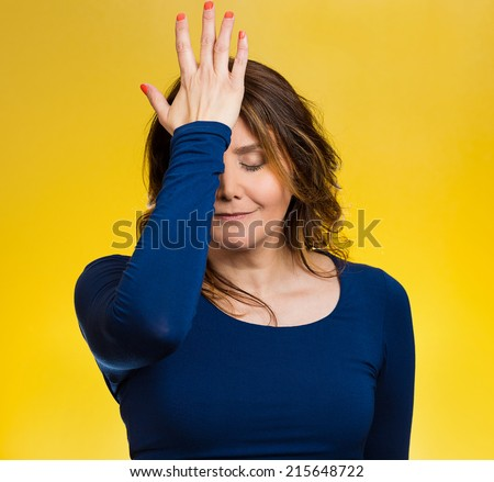 Portrait sad middle aged woman realizes mistake, regrets, slapping hand on head to say duh, isolated yellow background. Negative emotions, facial expression, feelings, body language, reaction - stock photo