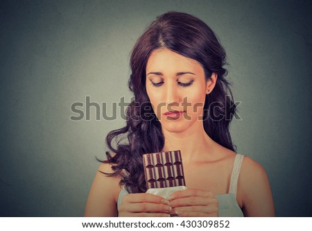 Portrait sad young woman tired of diet restrictions craving sweets chocolate isolated on gray wall background. Human face expression emotion. Nutrition concept. Feelings of guilt