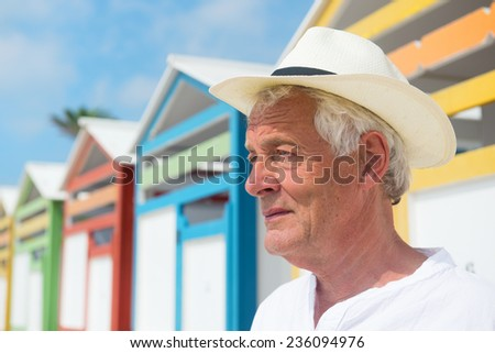 Portrait senior man at beach with colorful wooden huts - stock photo