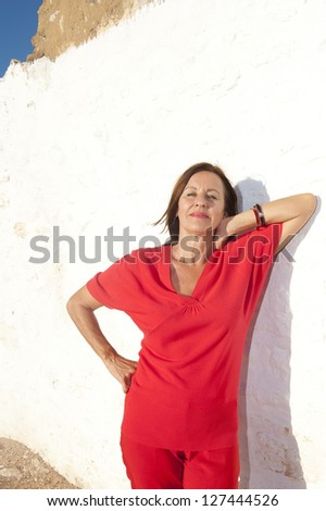 Portrait Sexy mature woman wearing red standing relaxed outdoor in front of old ruined building, isolated on white background. - stock photo