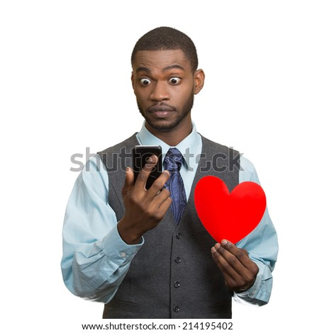 Portrait shocked young man, guy reading breaking news on smart phone holding red heart in his hand isolated white background. Human facial expression emotion feeling body language unexpected reaction - stock photo