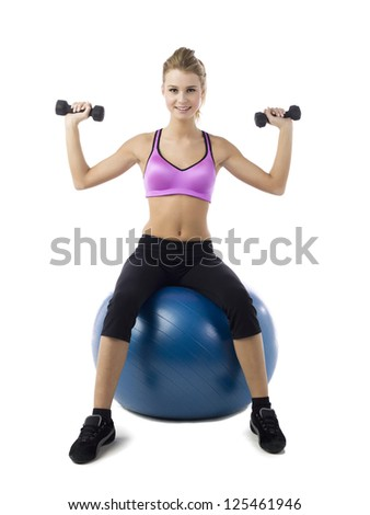 Portrait shot of a attractive female sitting on blue fitness ball with pair of dumbbells