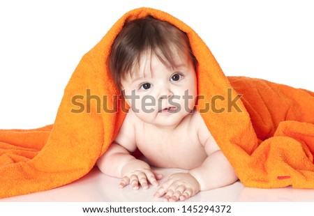 Portrait shot of a cute 6 months young baby lying under orange towel. Isolated on white. - stock photo