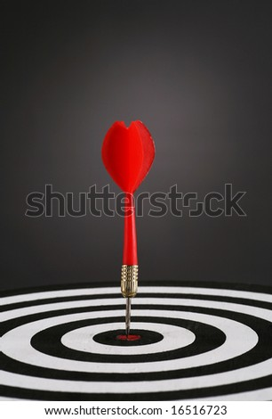 Portrait shot of a Red dart on bull's eye of a dart board - stock photo