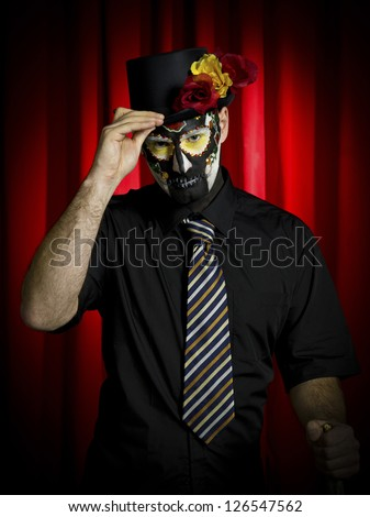 Portrait shot of a scary man wearing sugar skeleton and holding hat over red background. - stock photo
