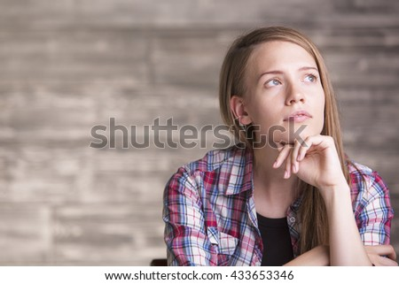 Portrait shot of pretty european woman in casual shirt with something on her mind - stock photo