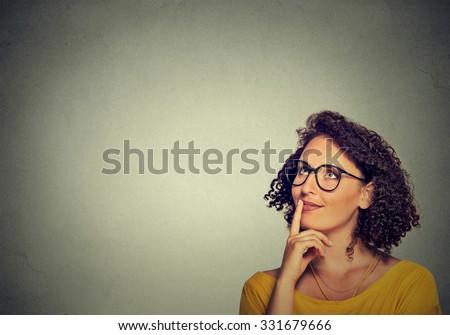 Portrait side profile happy beautiful woman thinking looking up isolated on grey wall background with copy space. Human face expressions, emotions, feelings, body language, perception - stock photo