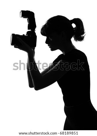 portrait silhouette in shadow of a young woman photographer holding a camera  in studio on white background isolated - stock photo