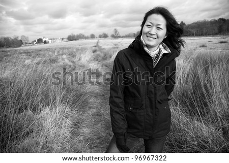 Portrait smiling asian woman, looking off into distance in the field - stock photo