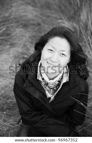 Portrait smiling asian woman looking up camera in the field - stock photo