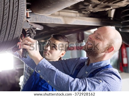 portrait smiling two men in coveralls working at auto repair shop closeup. - stock photo
