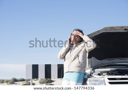 Portrait stressed mature woman breakdown with car calling for service, assistance for help on mobile phone, with blue sky as background and copy space.