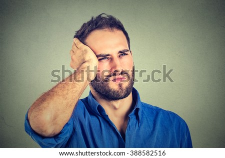 portrait stressed sad handsome young man looking up thinking  isolated on gray wall background. Human face expressions emotions. Unhappy guy with memory loss  - stock photo