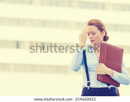 Portrait stressed worried unhappy young woman corporate employee having headache migraine  isolated outdoors on corporate office windows building background. Negative human emotions face expression   - stock photo