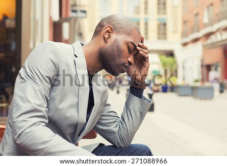 Portrait stressed young man hands on head with bad headache isolated city street background. Negative human emotion facial expression feeling - stock photo