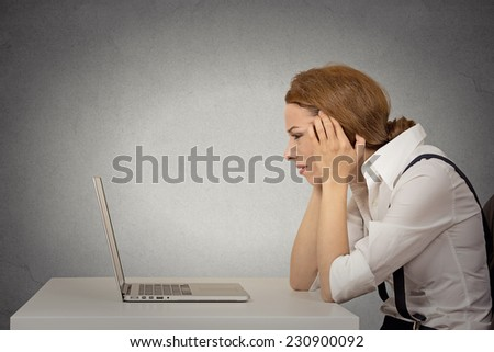 Portrait stressed young unhappy business woman working on laptop siting at desk isolated grey wall office background. Long working hours, complicated software concept. Negative face expression emotion - stock photo