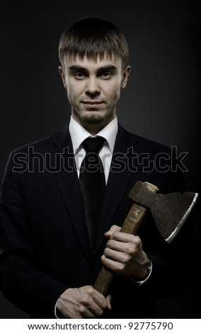 portrait  the  beautiful  businessman careerist in black costume and black necktie with axe - stock photo