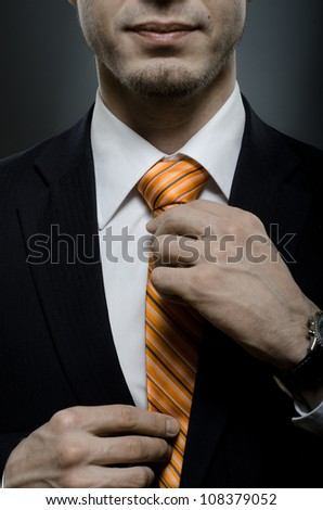 portrait  the  beautiful  businessman  in black costume tie one's necktie - stock photo