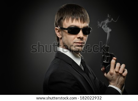 portrait the beautiful  man in black costume,  special-service agent or  body guard with  pistol