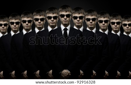 portrait  the  many beautiful  man in black costume,  multitude  special-service agent or  body guard - stock photo