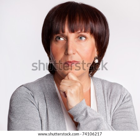 Portrait thinking mature woman looking away - stock photo