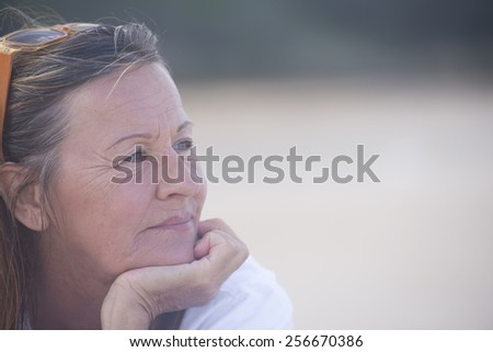 Portrait thoughtful attractive mature woman, laid back and relaxed chin on hand, peaceful confident outdoor, blurred background and copy space. - stock photo