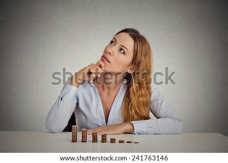 Portrait thoughtful young business woman corporate executive sitting at table with growing stack of coins isolated grey wall office background. Face expression. Financial economy doubt concept  - stock photo
