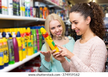 Portrait two attractive women choosing hair styiling mousse and smiling - stock photo