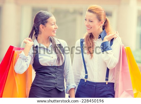 Portrait two happy, laughing young women carrying colorful bags talking walking in shopping mall, isolated outdoor street background. Positive human emotions, feeling, face expressions, lifestyle