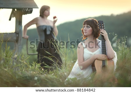 Portrait  two young women on the nature of the guitar at the well - stock photo