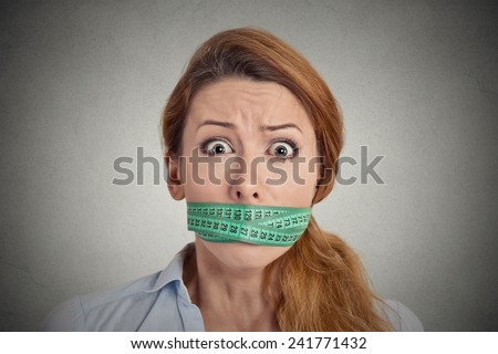Portrait unhappy young woman with green measuring tape covering mouth isolated grey wall background. Dieting lifestyle concept - stock photo