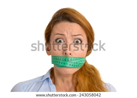 Portrait unhappy young woman with green measuring tape covering mouth isolated on white background. Dieting nutrition weight loss lifestyle concept  - stock photo