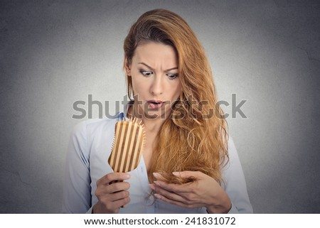 Portrait upset woman combing surprised she is losing hair, receding hairline. Face expression emotion - stock photo