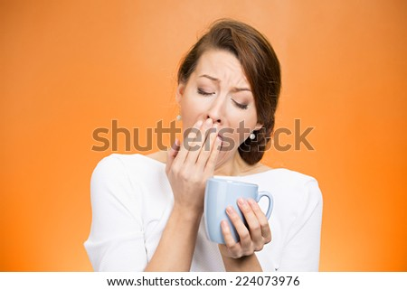 Portrait very tired falling asleep woman yawing employee holding cup coffee struggling not crash stay awake keep eyes opened isolated orange background. Human face expression, feeling emotion reaction - stock photo