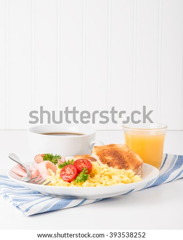 Portrait view of a plate of scrambled eggs and ham. - stock photo
