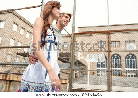Portrait view of an attractive teenagers couple walking together passed a college university building and sports ground holding each other during a weekend break in an urban city. Youth lifestyle. - stock photo