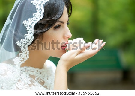Portrait with side view of one beautiful young brunette sensual pensive bride in white lace dress and veil on head looking away holding and eating cake, horizontal picture - stock photo