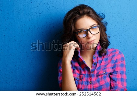 Portrait woman in glasses  on blue background. - stock photo