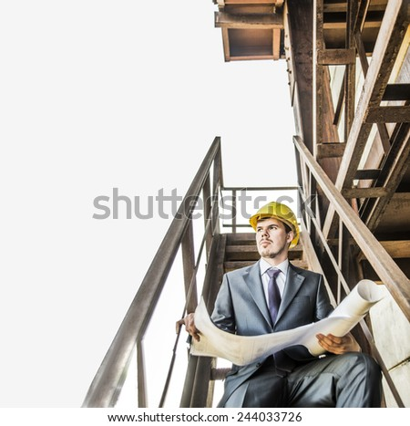 Portrait young adult caucasian male architect builder in yellow hardhat looking paper plan blueprint documents. Horizontal shape front view Serious Well dressed engineer sitting on metal rusty ladder - stock photo