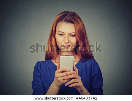 Portrait young angry woman unhappy, annoyed by something on cell phone skeptical while texting receiving bad sms text message isolated on gray wall background. Human face expression emotion reaction - stock photo