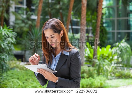Portrait young attractive businesswoman working with digital tablet at park. - stock photo