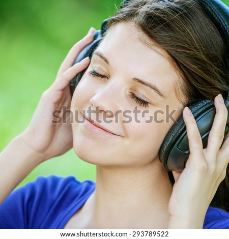 portrait young attractive girl headphones short hair green park - stock photo