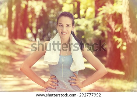 Portrait young attractive smiling fit woman with white towel resting after workout sport exercises outdoors on a background of park trees. Healthy lifestyle well being wellness concept  - stock photo