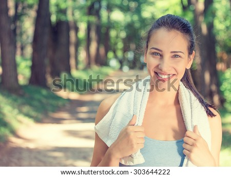 Portrait young attractive smiling fit woman with white towel resting after workout sport exercises outdoors on a background of park trees. Healthy lifestyle well being wellness happiness concept - stock photo