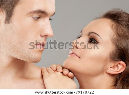 Portrait young beautiful couple on gray background. - stock photo
