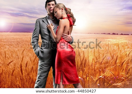 Portrait young beautiful couple under Golden wheat ready for harvest growing - stock photo
