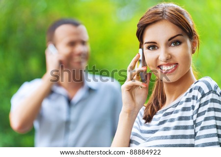 portrait young beautiful happy couple man woman talking phone background summer green park - stock photo