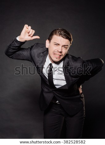 portrait young businessman in black suit holding hands on his aching back. emotions, facial expressions, feelings, body language, signs. image on a black studio background. - stock photo