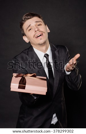 Portrait young businessman in black suit looking at camera with gift box. Christmas, x-mas, winter, valentine's day, birthday, happiness concept. Image on a black background.